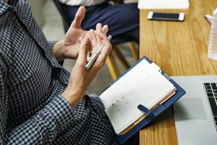 homme qui discute devant son carnet